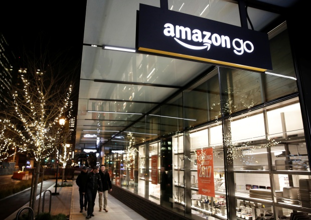 People walk by the Amazon Go brick-and-mortar grocery store without lines or checkout counters, in Seattle Washington